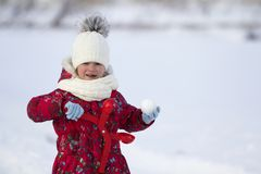 Cute little young funny toothless child girl in warm clothing playing having fun making snowballs on winter cold day on white brig stock photo