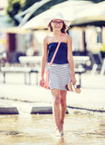 Cute little young teen girl walking on the fountain in hot summer day Royalty Free Stock Image