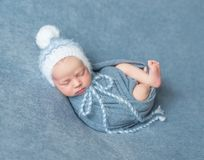 Cute llitle baby in hat covered with blue blanket sleeping