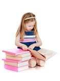 Cute long-haired Caucasian little girl reading a Royalty Free Stock Image