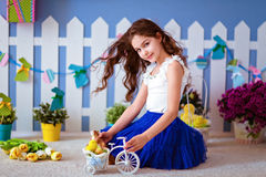 Cute long-haired young girl in a blue skirt sitting on the floor Stock Image