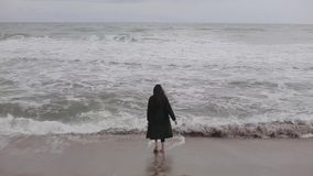 A beautiful barefooted girl in warm clothes runs towards the sea on a cold day, gets afraid of the cold water, and runs. A cute longhaired brunette in a long stock footage