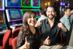 Couple having some fun in a casino. Cute looking couple going to the casino for a date and having some fun playing slots royalty free stock photos