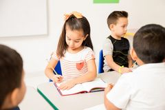 Hispanic preschool girl working in class. Cute looking Hispanic preschool girl doing a writing assigment during class at school royalty free stock photos