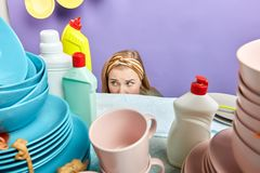 Cute lovely beautiful housewife hiding behind the kitchen table royalty free stock photos