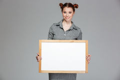 Cute lovely cheerful young woman standing and holding blank whiteboard Stock Photos
