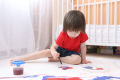 Cute lovely child painting with brush and gouache Stock Images
