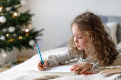 Cute lovely curly little female child lies on comfortable bed in her bedroom with decorated fir tree in background royalty free stock images