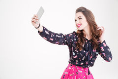 Cute lovely playful young woman taking selfie with mobile phone Stock Photo