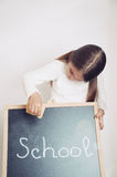 Cute lovely school girl holding chalkboard, education concept Stock Photo
