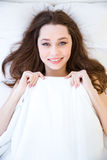 Cute lovely smiling young woman lying in bed Royalty Free Stock Photography