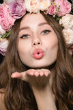 Cute lovely woman in beautiful flower wreath sending a kiss Royalty Free Stock Photos