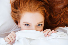 Cute lovely woman with red hair hiding under white blanket royalty free stock images