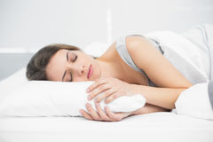 Cute lovely woman sleeping while lying on her bed Royalty Free Stock Images