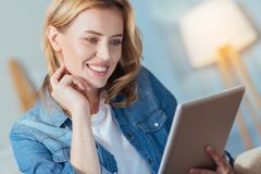 Cute lovely woman touching her chick while looking at the tablet royalty free stock images
