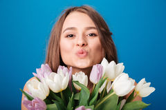 Cute lovely young woman with bouquet of tulips sending kiss Royalty Free Stock Image