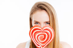Cute lovely young woman covered face with heatr shaped lollipop Royalty Free Stock Photo