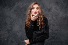 Cute lovely young woman with curly hair sending a kiss. Over grey background royalty free stock photo