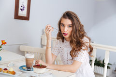 Cute lovely young woman eating dessert in cafe Stock Photos