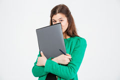 Cute lovely young woman in green jacket hiding behind folders Stock Photos