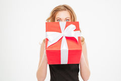 Cute lovely young woman hiding her face behing present box Royalty Free Stock Photos
