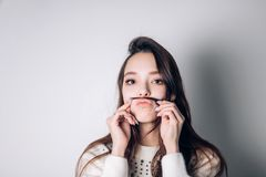 Cute lovely young woman making moustache with her hair stock photo