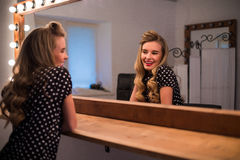 Cute lovely young woman with new hairstyle look in mirror Royalty Free Stock Image