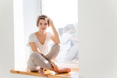 Cute lovely young woman in pajamas sitting on windowsill Stock Image