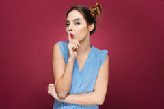 Cute lovely young woman showing silence gesture. Over pink background Stock Photography