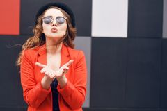 Cute lovely young woman in sunglasses, red jacket and fashion hat, standing and sending kiss over red and black background. stock photos