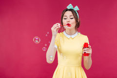 Cute lovely young woman in yellow dress blowing soap bubbles Royalty Free Stock Image