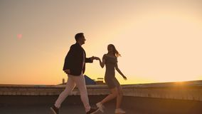 Cute lovers laughing running on the roof of the building at sunset on the background of the city and hugging standing at
