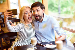 Cute loving couple photographing themselves in cafeteria Royalty Free Stock Photography