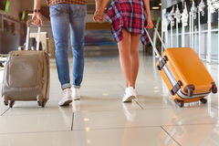 Cute loving couple is ready for trip. Close up of legs of young man and woman walking at airport with suitcases. They are holding hands Stock Photography