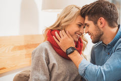 Cute loving couple relaxing at home. You are love of my love. Happy young men is touching female face with gentleness and smiling. Smartwatch on his arm Royalty Free Stock Photos