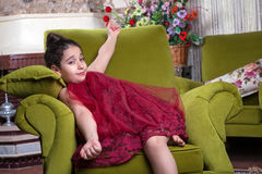 Cute lovlely middle eastern girl with dark red dress and collected hair posing and liying on green sofa at home interior. Royalty Free Stock Image