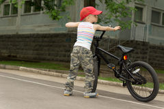Cute macho little boy with his bicycle Royalty Free Stock Photography