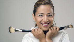 Cute Make-up Artist with Brushes. Pretty smiling Makeup Artist holding an assortment of make-up brushes Royalty Free Stock Photo
