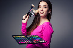 Cute make-up artist holding her vast palette of colors Stock Photography