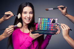 Cute make-up artist holding her vast palette of colors and hands Stock Image