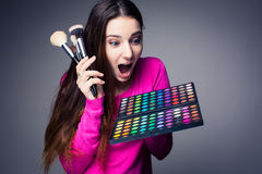 Cute make-up artist holding her vast palette of colors Stock Images
