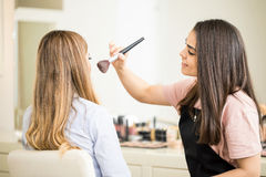 Cute makeup artist using a brush. Profile view of a pretty makeup artist using a brush to put some blush on a customer in her salon Royalty Free Stock Images
