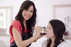 Cute makeup artist at work. Beautiful makeup artist working on a client in a beauty salon Royalty Free Stock Photos