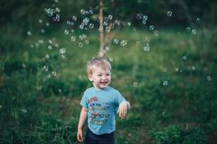 Cute male child catches soap bubbles in nature three years old blonde hair.  stock images