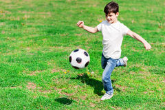 Cute male child is playing football Stock Image