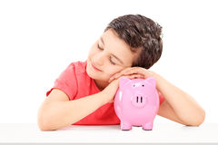 Cute male child sleeping on a piggybank. Isolated on white background Royalty Free Stock Images