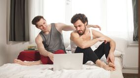 Cute male gay couple spend time at home. They are sitting down on a sofa and use the laptop.