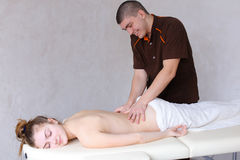 Cute male massage therapist does restoring procedure for back of Royalty Free Stock Images