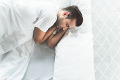 Cute male person having nap on bedding royalty free stock photo