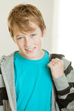 Cute male student in blue shirt and gray sweater. Cute smiling male hazel eyed student in aqua colored shirt and gray sweater with backpack strap being held over stock photos